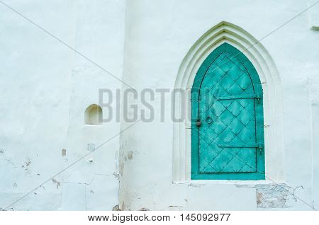 Old turquoise metal forged door with arcade on the white stone wall of the medieval Slavic church of Fedor Stratilates in Veliky Novgorod Russia. Architecture view.