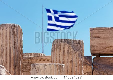 Antique ruins of the Acropolis and the greek flag on background; focus on ruins. Acropolis of Athens Greece