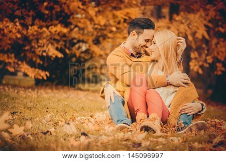 Beautiful embraced couple in the park.Happy couple having fun in autumn park.