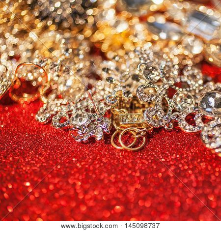 Close up of collection of assorted gemstone jewellery on red shiny glitter background