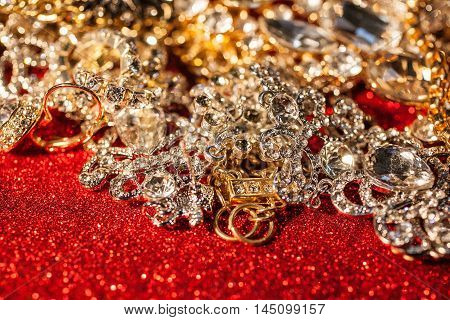 Close up of collection of assorted golden and silver jewellery on red shiny glitter background