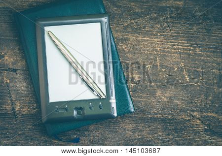 Black ereader with notebook in leather cover and ink pen on vintage old rustic wooden table. Blank E-book reader. New technologies in education. Back to school concept. Top view. Copy space.