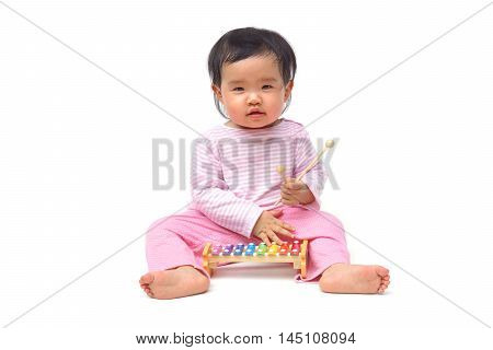 Asian baby playing with a colorful xylophone