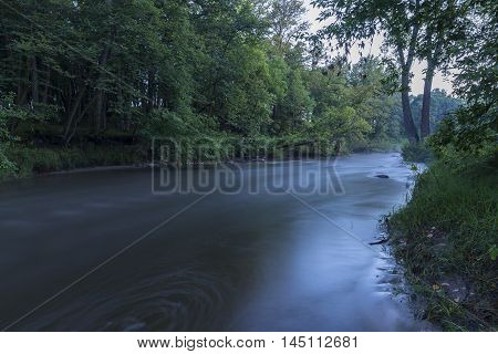 A flowing river in the woods in the evening.