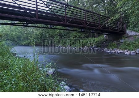 A flowing river under a bridge in the evening.