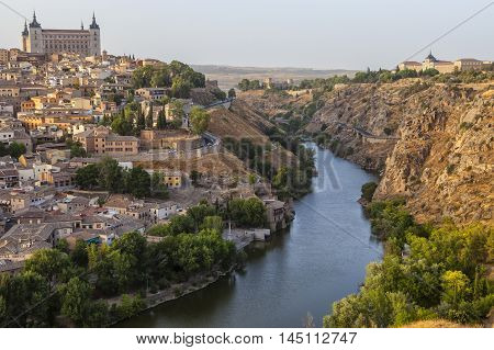 Old town cityscape with Alcazar and river Tagus at sunset Toledo Spain