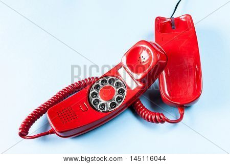 Old red phone off the hook on blue background