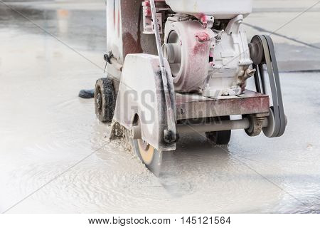 Worker Cutting Concrete Road With Diamond Saw Blade Machine