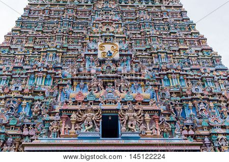 Madurai India - October 19 2013: Part of the East Gopuram of the Meenakshi Temple fills entire photo. Abundance of pastel colored statues of gods goddesses and more.