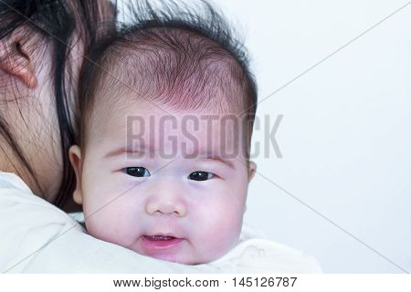 Mother and baby. Lovely asian girl smiling and resting on her mother's shoulder. Happy family spending time togetherness. Mother's Day celebration.