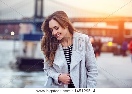 Beautiful happy woman walking near East River in New York City and looking down