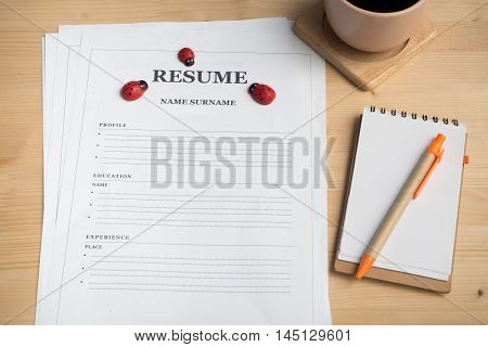 Office desk with resume information Black coffee note paper and pencil. View from above resume information.