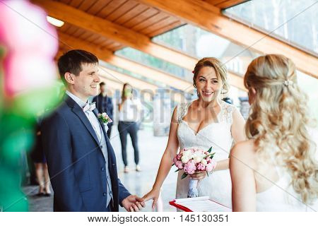 Portrait of happy newly married couple and guests at wedding ceremony
