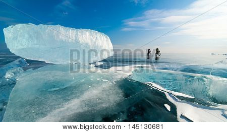 Two bike tourists riding on the black cracked ice surface of frozen lake with hummocks