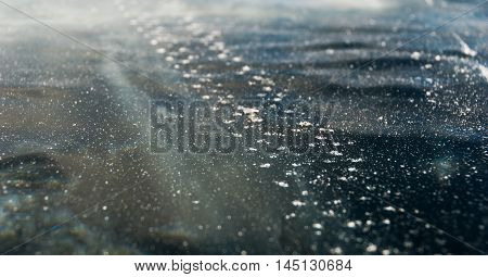 Trace of studded bicycle tires on the black ice surface of frozen lake. Nature abstract background
