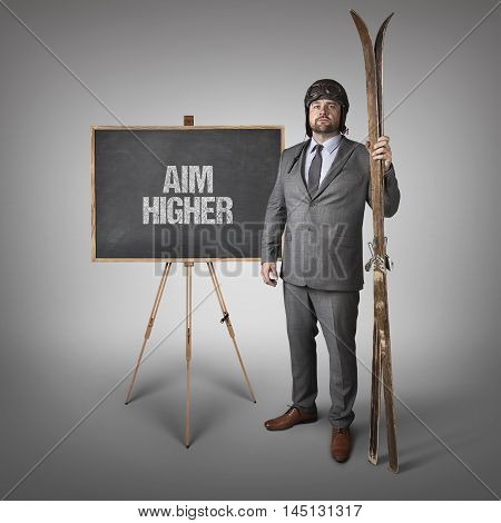 Aim higher text on blackboard with businessman and skis
