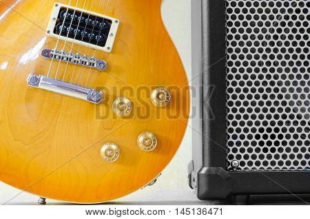 Electric guitar and amplifier isolated on a light brown