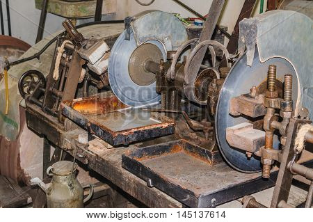 Old grindstone. Old stone cutting machine with water cooling.