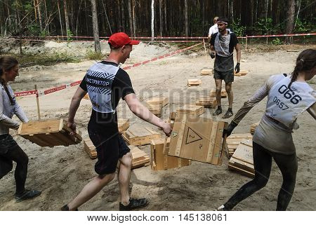 Tyumen, Russia - June 11, 2016: Race of Heroes project on the ground of the highest military and engineering school. Transfer of boxes stage. Athletes bear box with cartridges weighing 28 kilograms