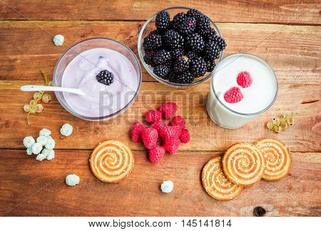 Products served for breakfast or snack, yoghurt in a glass bowl, kefir, cookies with sesame seeds and fresh ripe raspberry and blackberry