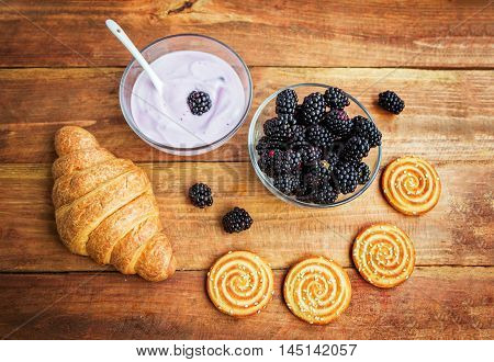 Products served for breakfast or snack, yoghurt in a glass bowl, croissant, cookies with sesame seeds and fresh ripe blackberry on wooden surface, topview,