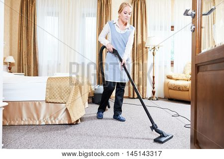 Hotel service. female housekeeping worker with vacuum cleaner
