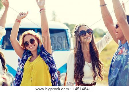 nature, summer, youth culture and people concept - happy young hippie friends dancing over minivan car outdoors