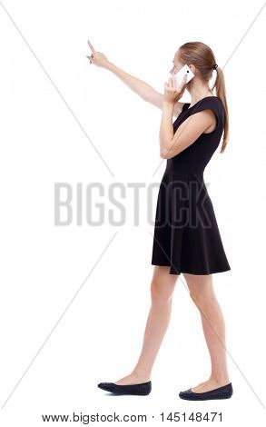 side view of walking woman. Rear view people collection. Isolated over white background. Blonde in a short black dress talks on the phone about what I heard.