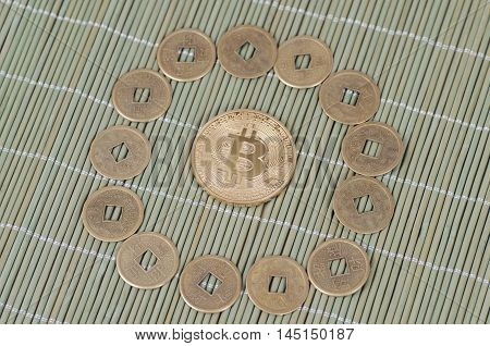 Gold-plated Bitcoin on a wooden tablecloth. Selective focus.