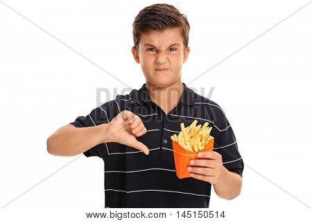 Disappointed kid holding a bag of fries and making a thumb down sign isolated on white background
