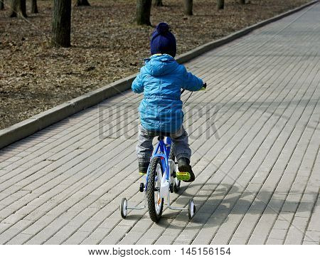 The image of the child who is riding a children's Bicycle. Rear view.
