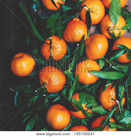 Tangerines with leaves on wooden background. Mandarins Tangerine Closeup. Rustic style