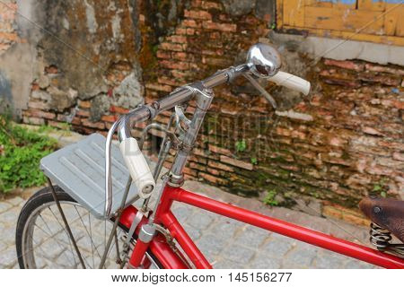 Vintage bike handlebar Red bicycle near the window of old brick wall home background