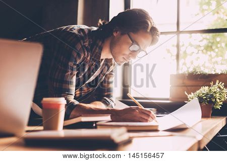 Time to work. Confident young man in casual wear sketching on blueprint while standing near wooden desk in creative office