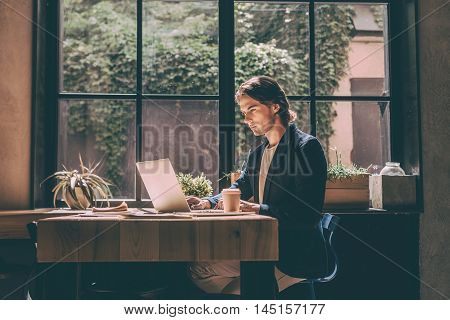 Full concentration at work. Confident young man in smart casual wear looking at laptop while sitting near window in creative office or cafe