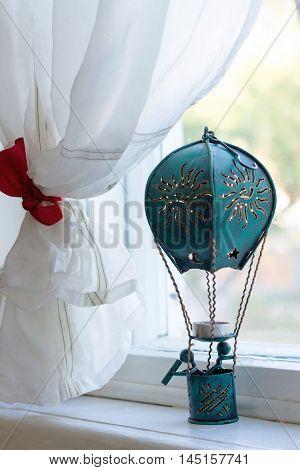 Dark blue toy air balloon is standing on white window sill