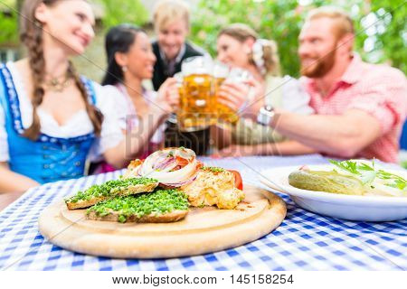 Five friends, women and men, sitting in beer garden clinking glasses having Bavarian appetizers on the table