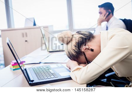 Young Asian business woman taking nap in office being exhausted and overworked
