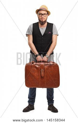 Young hipster holding a suitcase isolated on white background