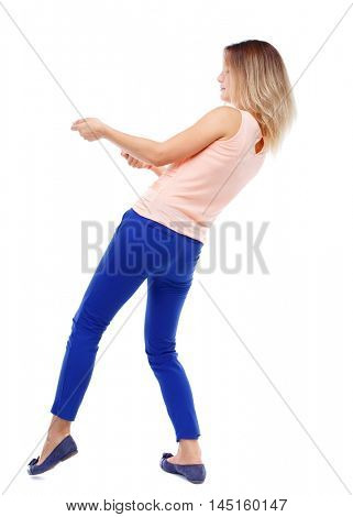 back view of standing girl pulling a rope from the top or cling to something. Isolated over white background. The blonde in a pink shirt pulling rope side.