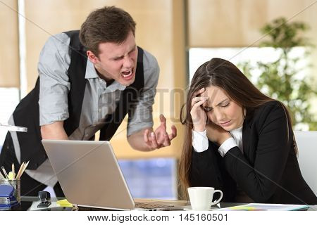 Bullying with an out of control boss shouting to a stressed employee in a desktop at office interior