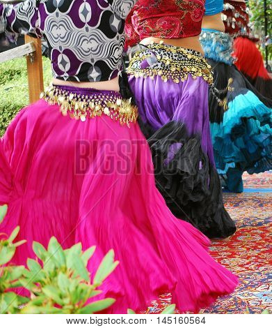 Belly dancers in colorful costumes performing on stage.