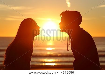 Side view of a couple silhouette of teenagers kissing the sun with love at sunset on the beach with the horizon in the background