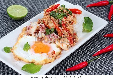 Rice topped with stirred  minced-pork ,squid ,basil and fried egg(sunny up) on black napery.