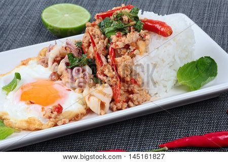 Rice topped with stirred  minced-pork ,squid ,basil and fried egg(sunny up) on black napery. Selective focus.