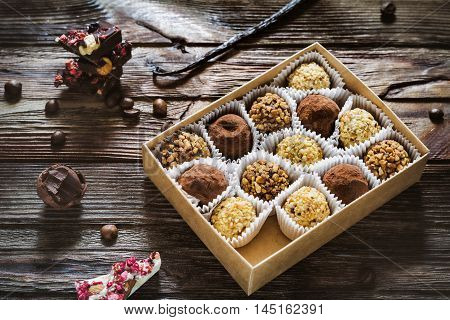 Chocolate truffles in a box and chocolate barks on wooden table