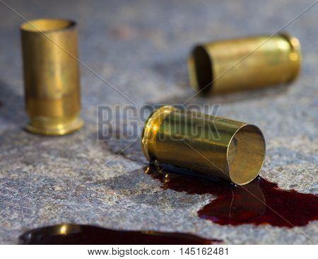 Handgun casings on concrete with blood around the brass