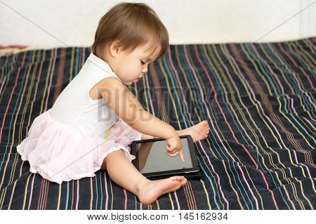 Little baby girl touching a Tablet PC touch screen with finger cute