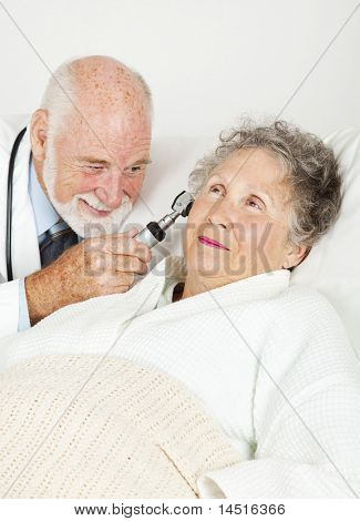 Doctor uses an otoscope to check inside his senior patient's ears.