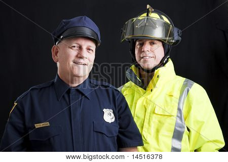 Public employees, a firefighter and a police officer, smiling and happy.  Black background.